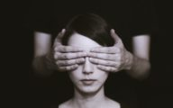 Femme aux yeux masqués par des mains